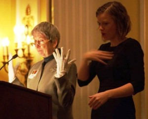 "Katharine Gibbs was honored in March 2014 as a woman of character, courage, and commitment. Rose Doherty shows the audience her white gloves as the interpreter signs ""white."""