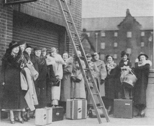 Boston students leaving from South Station to go to Manhattan.  Nothing bothers them so they can pose underneath a ladder!